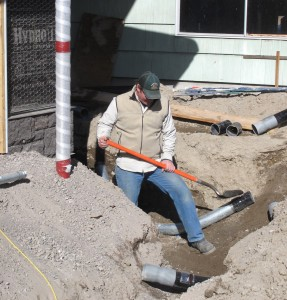 Mike Wagnon with A.P.E.S. works in the trench to install electrical conduit.