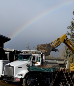 A rainbow brings beauty to the rough and rugged process of excavation and rock hauling.