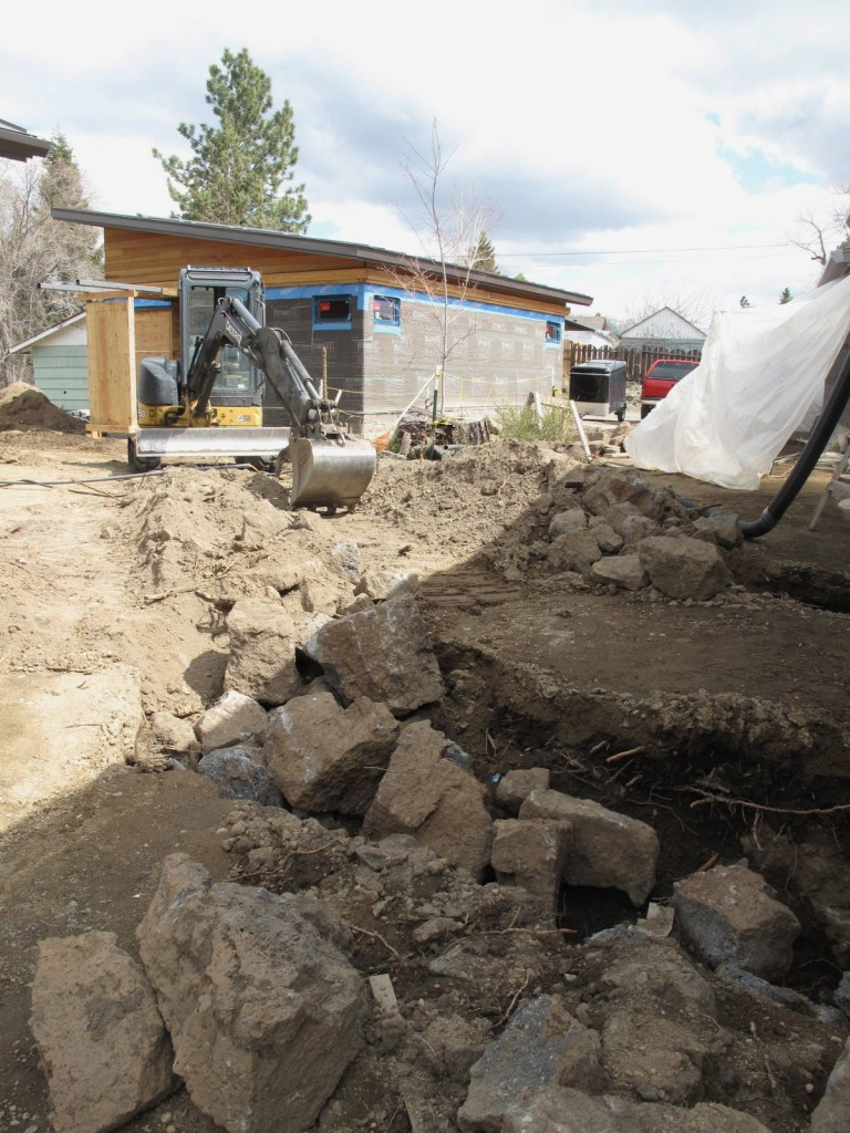Rock is hammered out of trenches and holes, piled, then hauled away for crushing.