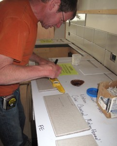 Doug Cahail measuring tiles for some custom cutting.
