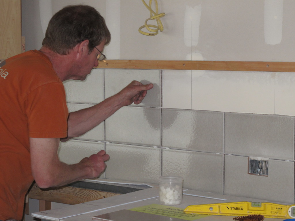Doug Cahail installing the backsplash in the kitchen. The ceramic tiles are made from 70% recycled waste materials.