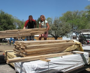 Sonny and Anna unloading the stacks of Myrtlewood flooring on May 9. The flooring needed to acclimate for a few weeks before installation.